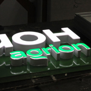 Illuminated channel letters embossed in a composite panel sign
